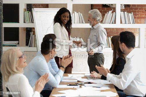 815703312 istock photo Before starting training boss presenting african coach to diverse staff 1186603931