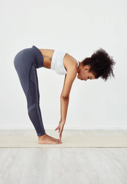 Before you work it out, stretch it out Shot of a young woman stretching during her workout routine at home touching toes stock pictures, royalty-free photos & images