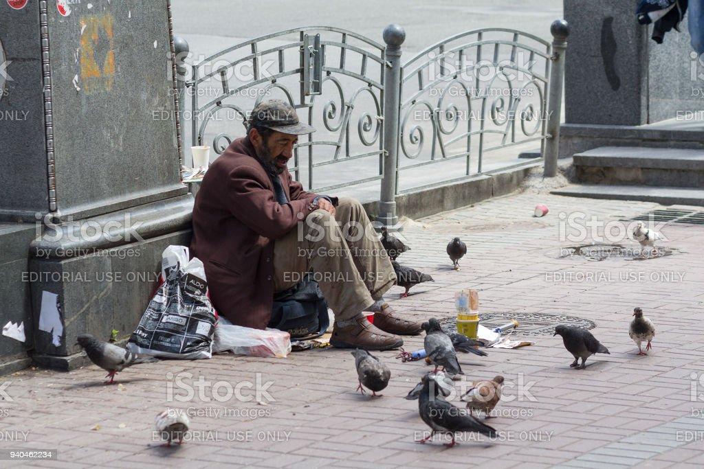 Beggar begging for alms sitting on the sidewalk stock photo