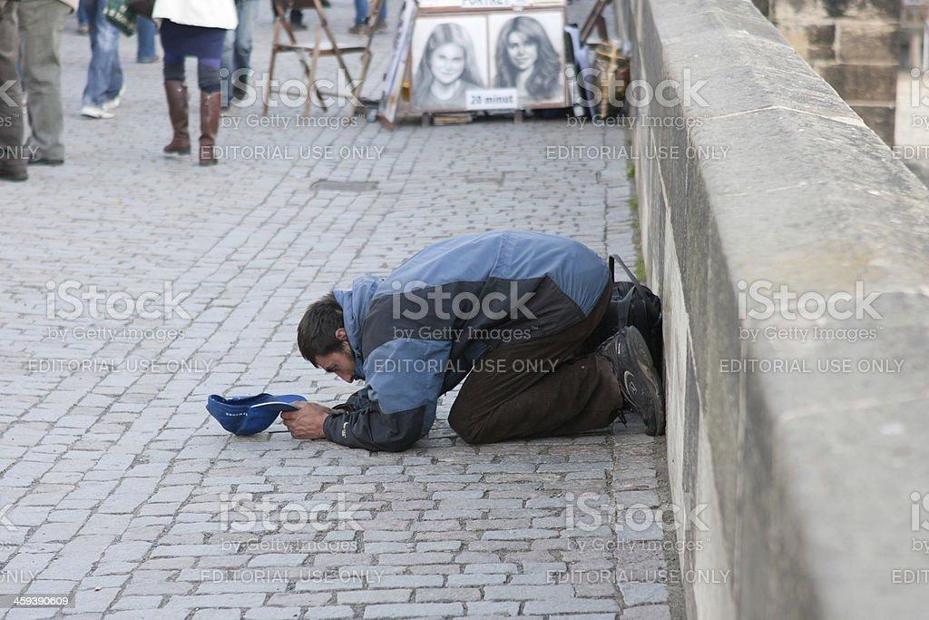 Beggar on Charles Bridge stock photo