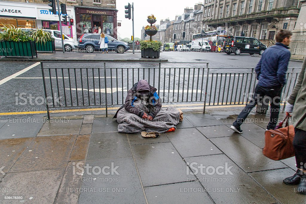 Beggar Sitting on the Pavement stock photo