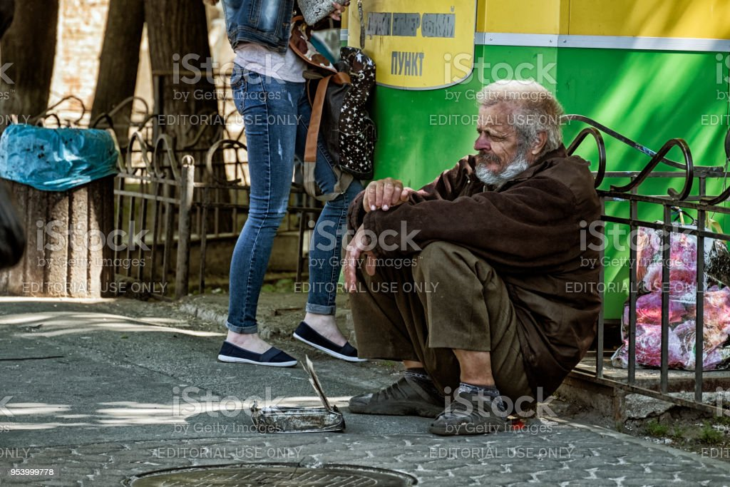 Beggar squatted down and begging stock photo