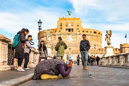 868668568 istock photo Beggar woman asking alms on her knees on Ponte Sant'Angelo, Bridge of Hadrian full of walking people with Castel Sant'Angelo, Castle of Holy Angel on the background 1126230577