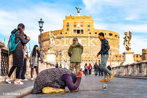 868668568 istock photo Beggar woman asking alms on her knees on Ponte Sant'Angelo, Bridge of Hadrian full of walking people with Castel Sant'Angelo, Castle of Holy Angel on the background 1126230604