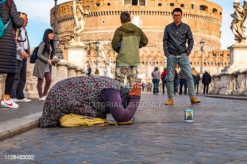 868668568 istock photo Beggar woman asking alms on her knees on Ponte Sant'Angelo, Bridge of Hadrian full of walking people with Castel Sant'Angelo, Castle of Holy Angel on the background 1128493032