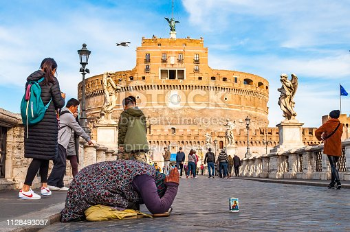 868668568 istock photo Beggar woman asking alms on her knees on Ponte Sant'Angelo, Bridge of Hadrian full of walking people with Castel Sant'Angelo, Castle of Holy Angel on the background 1128493037