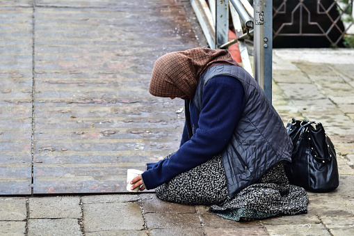 Milan, Italy - April  27, 2019: Beggar woman begging for money passersby kneeling on the ground