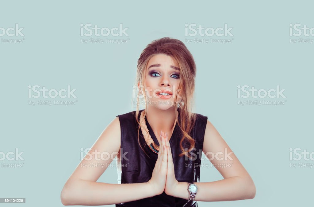 Begging. Closeup portrait sad young woman praying, hoping for the best, going through tough times in her life, isolated on light green background wall with copy space. Human emotion, facial expression stock photo