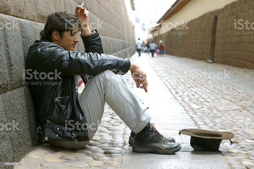 Begging man sitting near Inca wall in Cuzco, Peru royalty-free stock photo