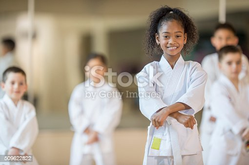 A multi-ethnic group of elementary age children are standing together in formation during their taekwando class. One girl is smiling while looking at the camera.
