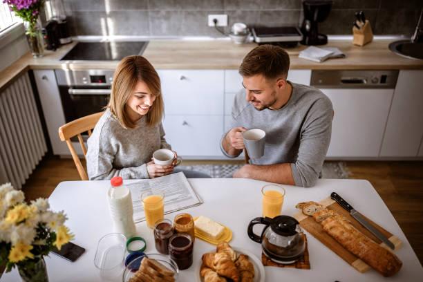 comenzando su día con un desayuno saludable - happy couple sharing a cup of coffee fotografías e imágenes de stock