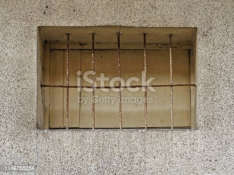 window with rusty iron grid