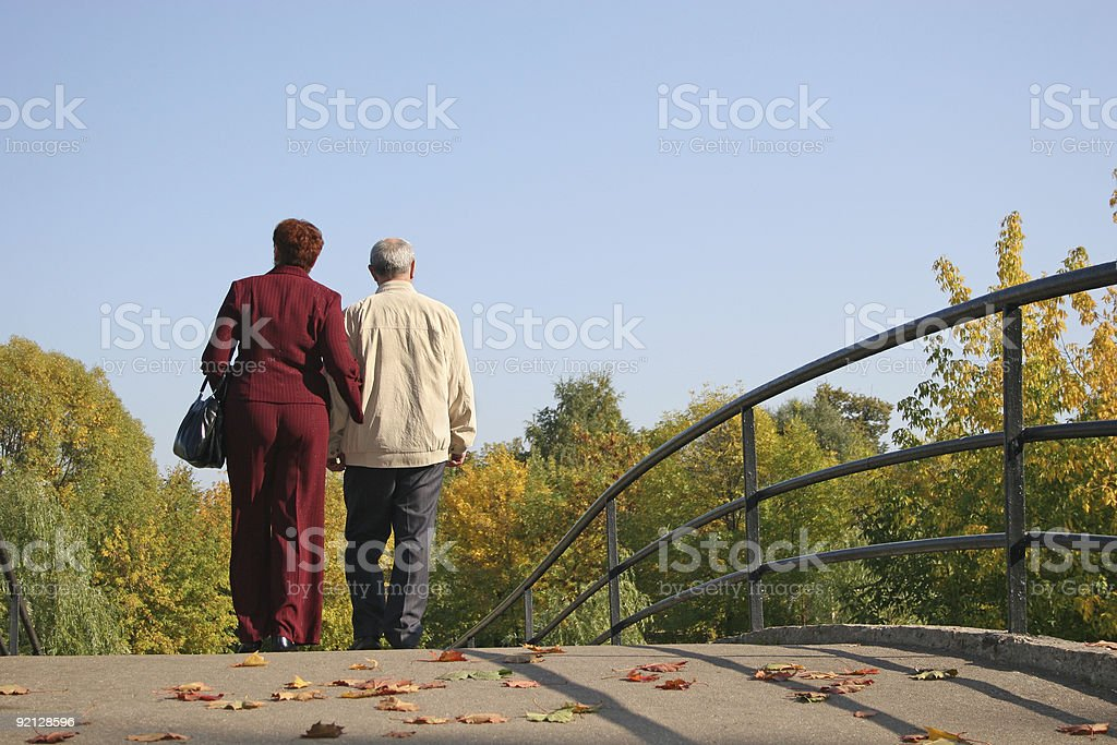 behind couple on autumn bridge royalty-free stock photo