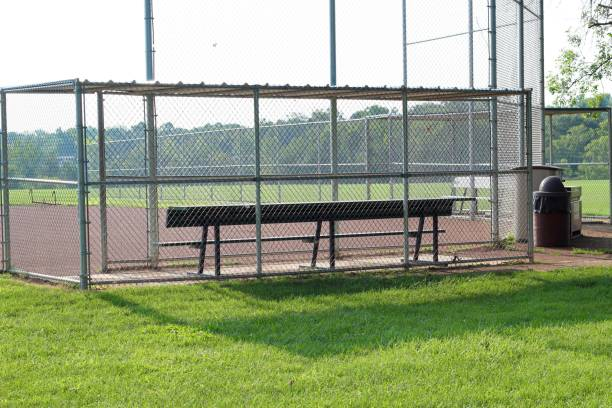 Behind Dugout A view from behind the dugout at the baseball field on a sunny summer day. baseball diamond stock pictures, royalty-free photos & images