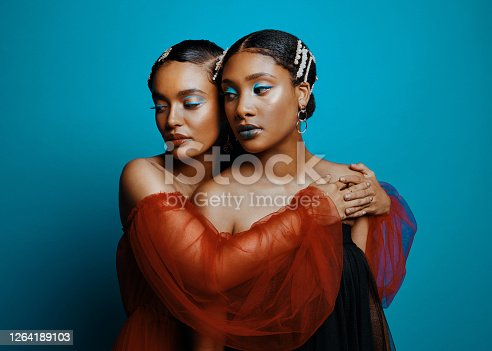 Shot of two beautiful young women wearing mesh dresses while posing against a blue background