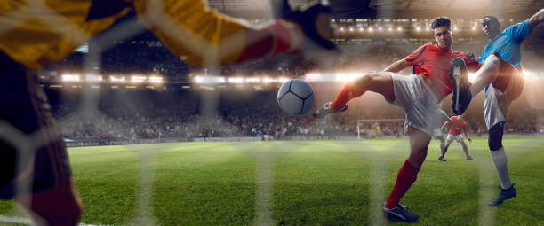 Behind Goal Net View of Footballer Volleying to Score Goal stock photo