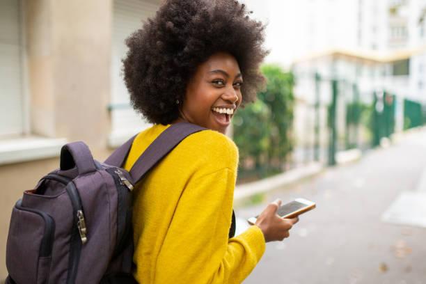 hinter der lachenden afro amerikanischen Frau mit Tasche und Handy zu Fuß auf der Stadtstraße – Foto
