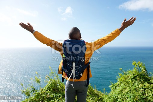 Portrait from behind of male hiker with arms outstretched
