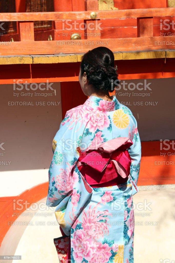 265fd49ee1a7 Derrière de femme en robe Kimono bleu et ceinture rose profond dans les  temples japonais.