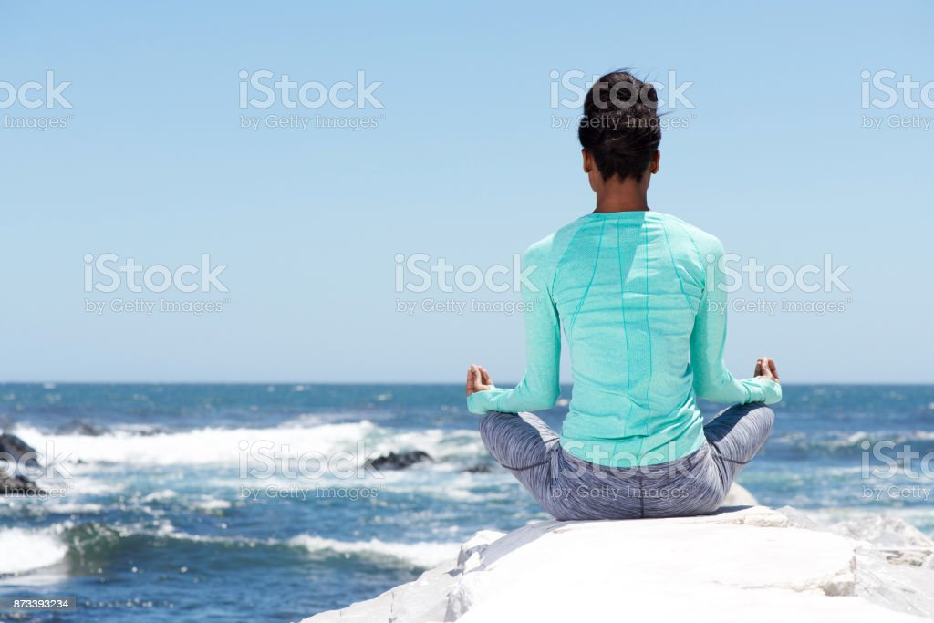 behind of yoga woman at the beach stock photo