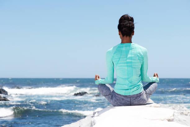 behind of yoga woman at the beach - prendersi cura del corpo foto e immagini stock