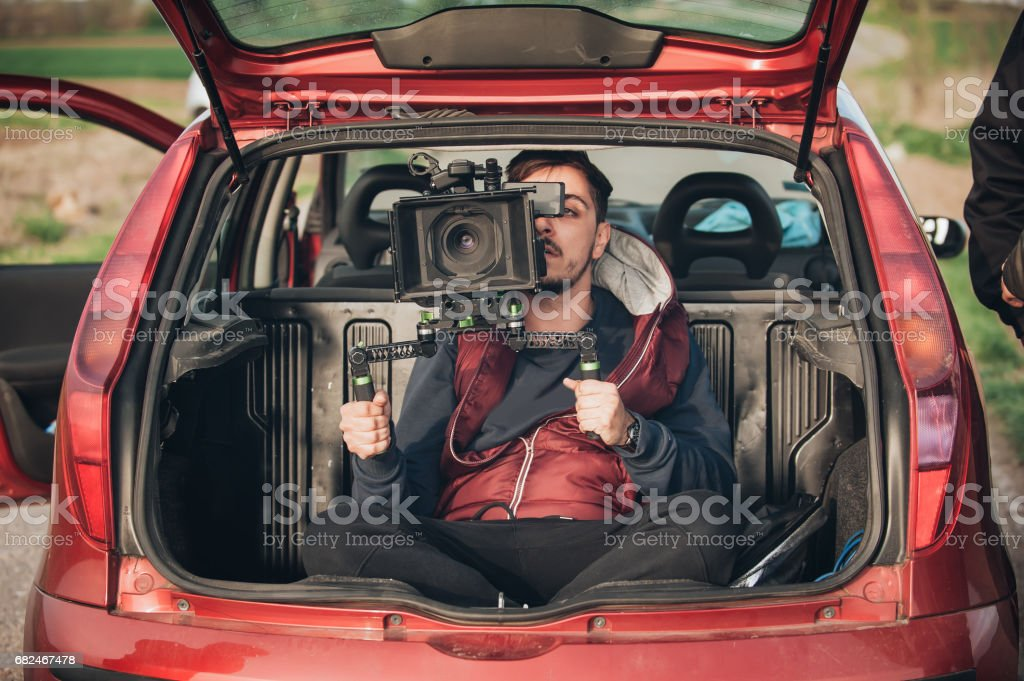 Behind scene improvisation. Cameraman from trunk of car shooting film stock photo
