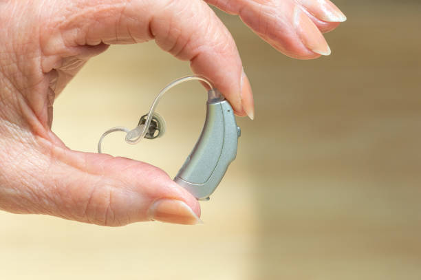 Behind The Ear hearing aid held between pensioners fingers. stock photo