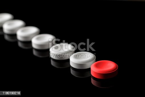 Behind the red pill are lined up white pills. One red and many white pills on a black background. With blur in perspective. Concept on leadership and features. From left to right. Top down.