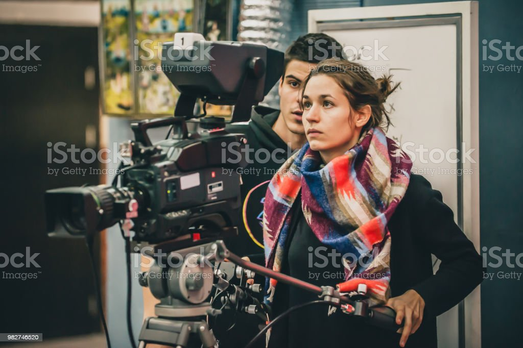 Behind the scene. Cameraman and assistant shooting film with camera royalty-free stock photo