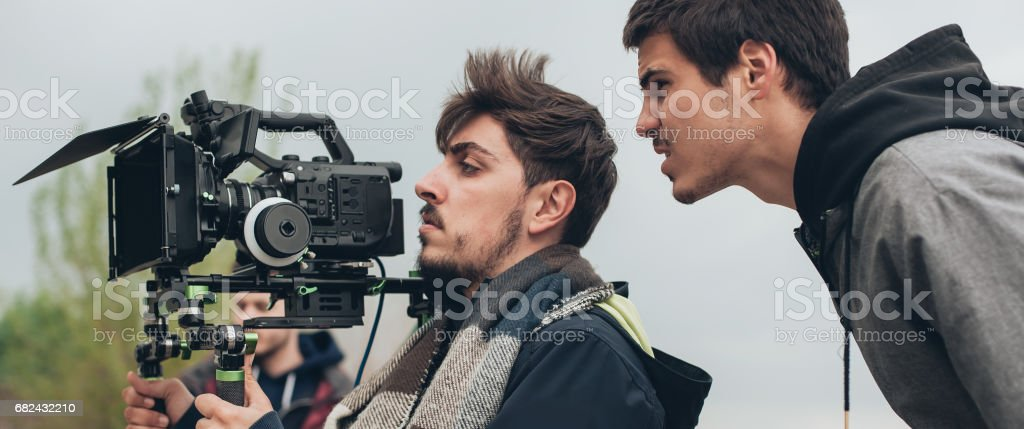 Behind the scene. Cameraman and film director shooting film scene stock photo