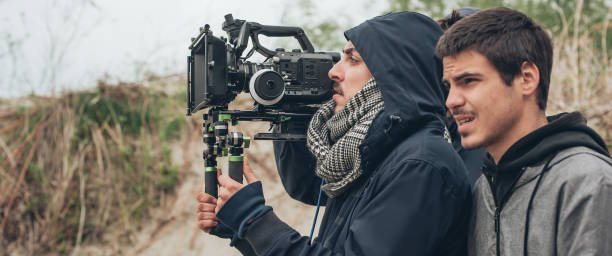 behind the scene. cameraman and film director shooting film scene - film director stock pictures, royalty-free photos & images