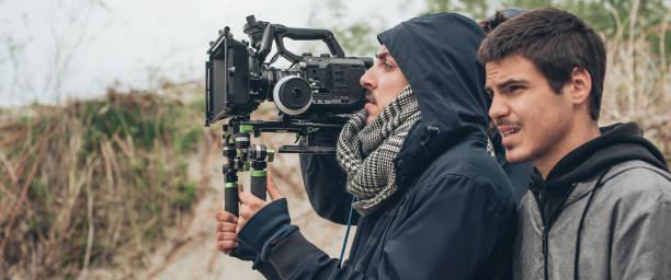 Behind the scene. Cameraman and film director shooting film scene stock photo
