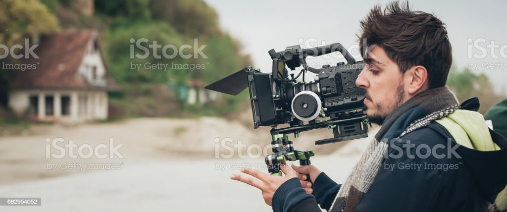 Behind the scene. Cameraman shooting film scene with his camera royalty-free stock photo