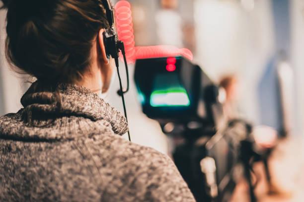 hinter den kulissen. weibliche kameramann shooting filmszene mit kamera - dokumentation stock-fotos und bilder