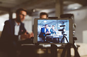 Two bloggers on digital tablet screen. Businessman with male guest recording a video blog on camera. Behind the scenes of a business vlog.