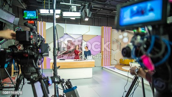 Photo of video recording equipment and stage in a studio during the filming of a TV show.