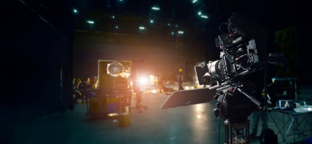 Behind the scenes of making of movie and TV commercial. Camera of movie and video production. Film Crew. B-roll, and crew team in studio and set on dark background stock photo