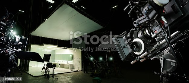 Behind the scenes of making of movie and TV commercial. Camera of movie and video production. Film Crew. B-roll, and crew team in studio and set on dark background