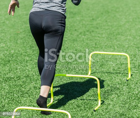 976685710 istock photo Behind view of female running over mini hurdles 975221664