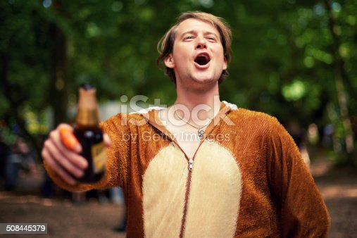 Shot of a young man drinking outside while dressed in a bear suit
