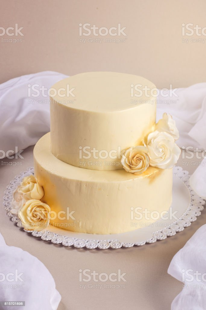 Beige 2 Tiered Wedding Cake Decorated With Mastic Roses Stands On ...