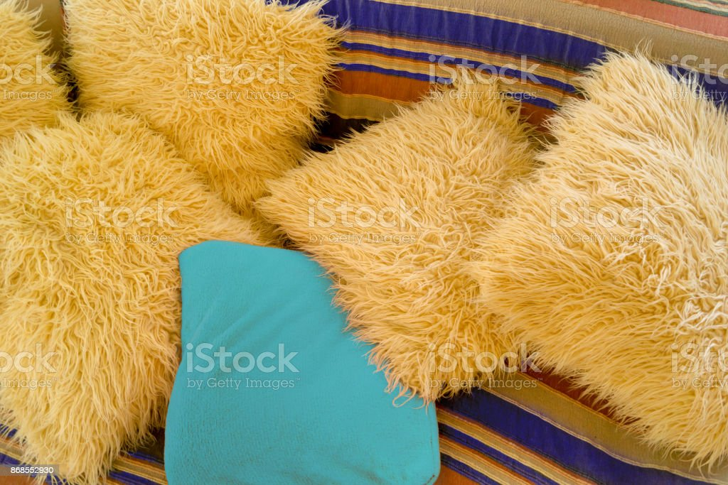 Beige and blue artificial wool cushions on the striped couch stock photo