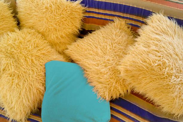 künstliche wolle in beige und blau kissen auf dem gestreiften sofa - teppich hellblau stock-fotos und bilder