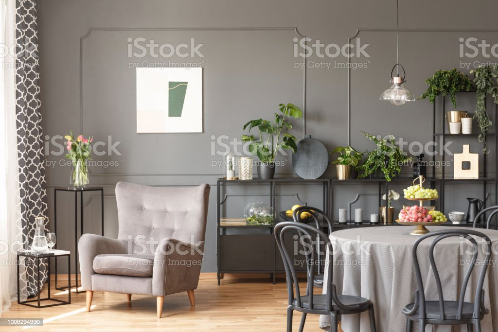 Beige armchair against grey wall with poster in flat interior with chairs at table. Real photo stock photo