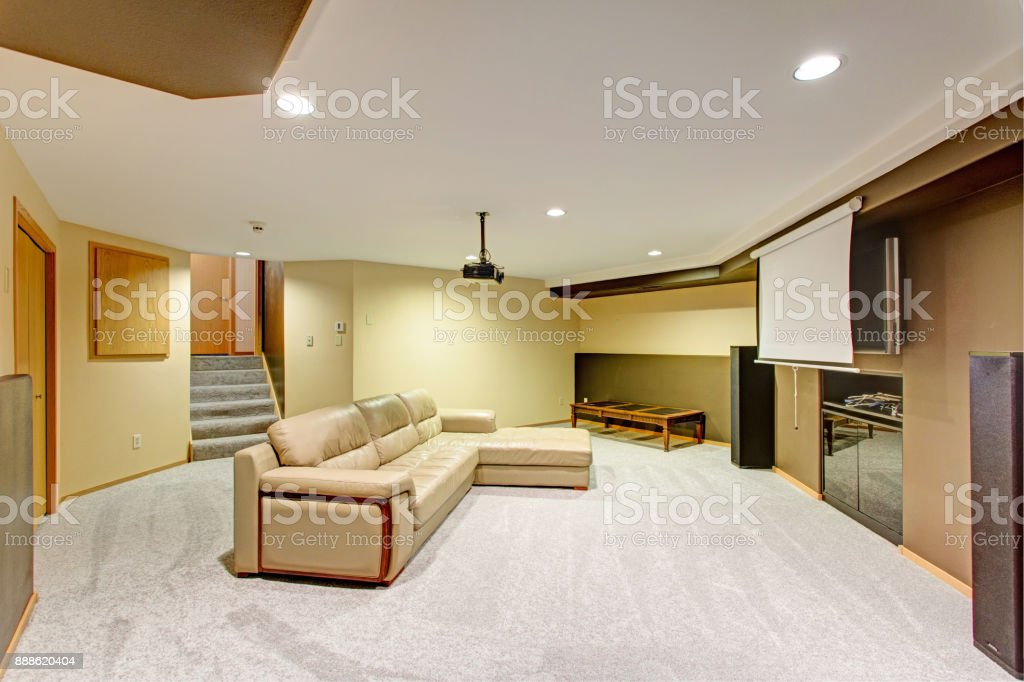 Beige basement movie room with a leather sectional stock photo