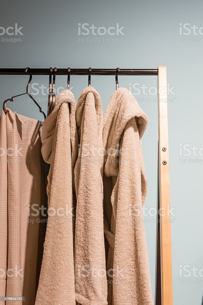 beige bath robe hanging on a wooden rack stock photo