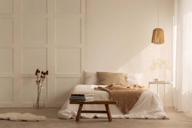beżowy koc na podwójnym łóżku w stylowej sypialni wabi sabi w minimalistycznym domu, prawdziwe zdjęcie z kopią miejsca na pustej ścianie - beżowy zdjęcia i obrazy z banku zdjęć