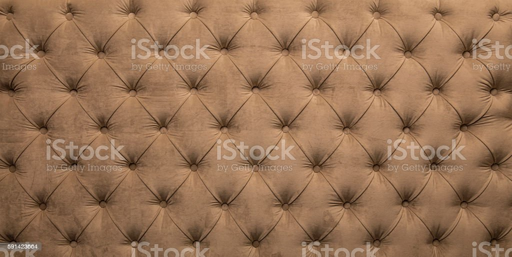 Beige capitone tufted fabric upholstery texture stock photo