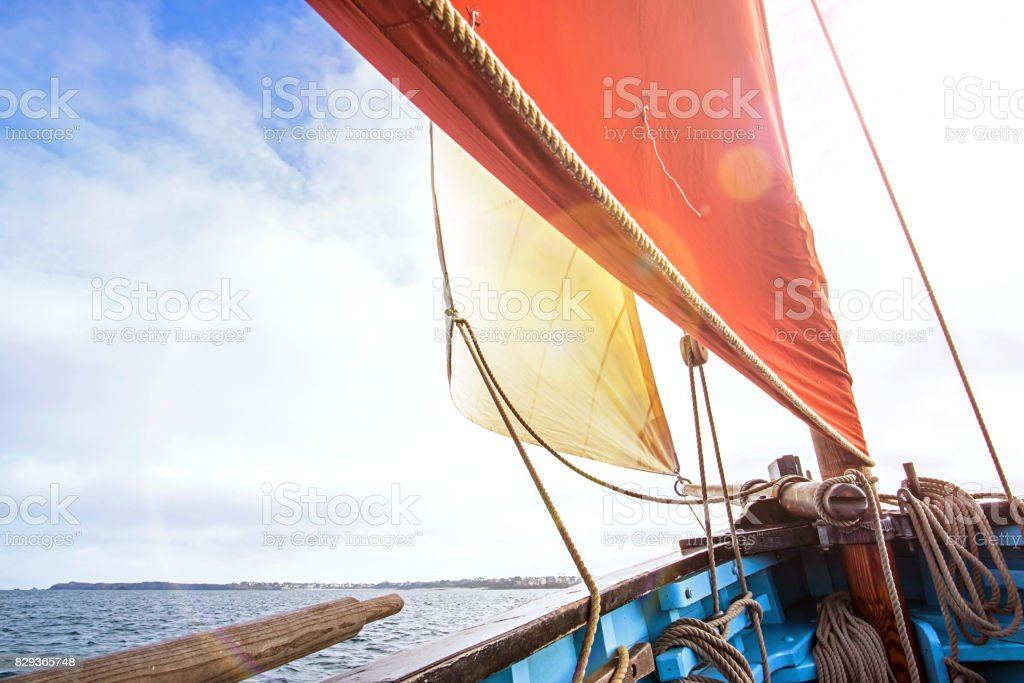 beige cotton jib sail and an ocher sail blow up by the wind with wooden mast, bowsprit and hull of an old rigging sailing boat stock photo