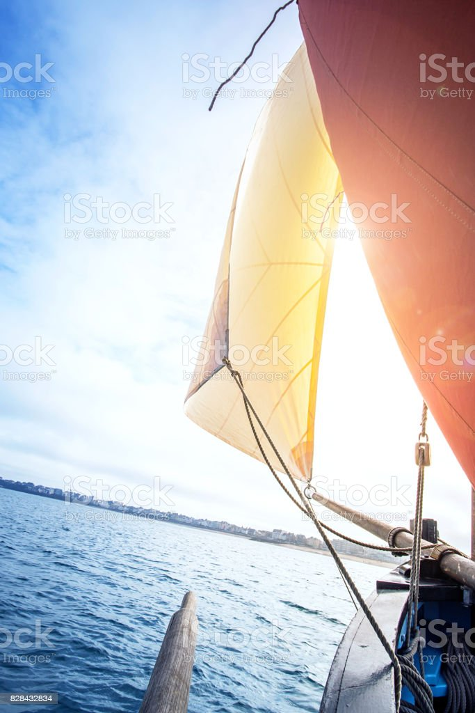 beige cotton jib sail and an ocher sail filled by the wind with wooden mast, bowsprit and hull stock photo